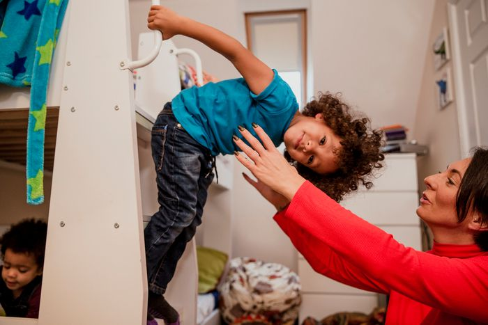 Young boy on bunk bed stairs playing with his mother