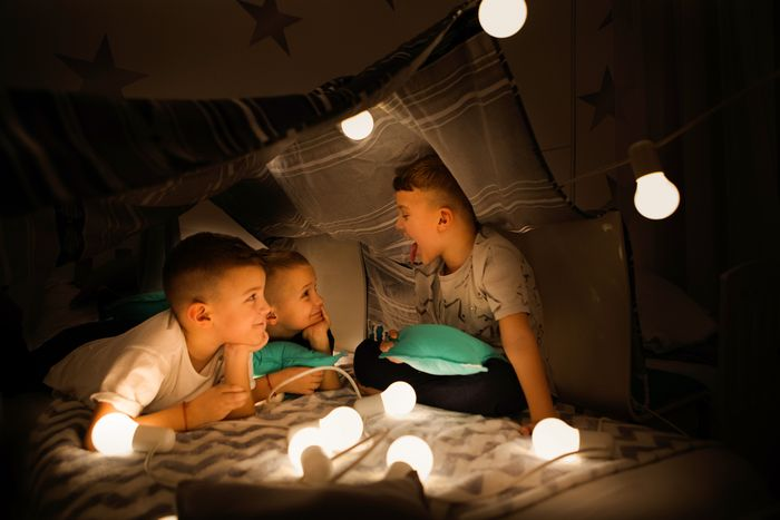 Three young boys playing in blanket fort illuminated by string lights