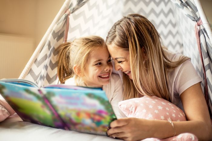 Smiling mother reading a storybook to her young daughter inside a bed tent