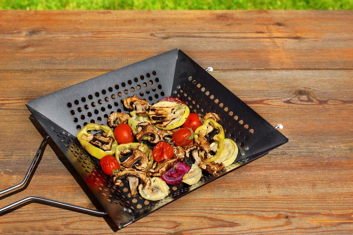 grilled vegetables mix in a cast iron basket on wood table