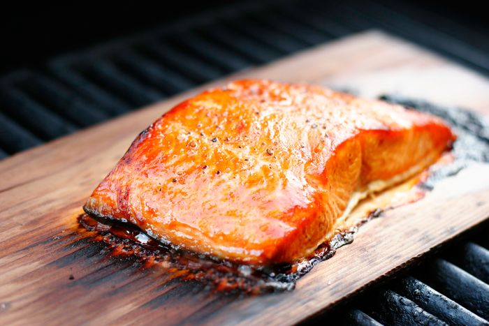 Salmon fillet with coarse ground pepper, grilled over a cedar plank