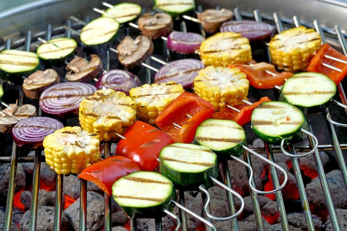 mixed vegetable skewers on a charcoal grill