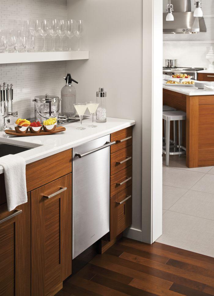 A clean, white mini bar leading into a kitchen, with white walls and brown wooden cabinets. A dishwasher is built into the cabinets with cocktail fixings on the counter.