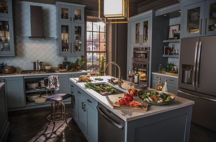 A blue kitchen full of GE slate appliances.