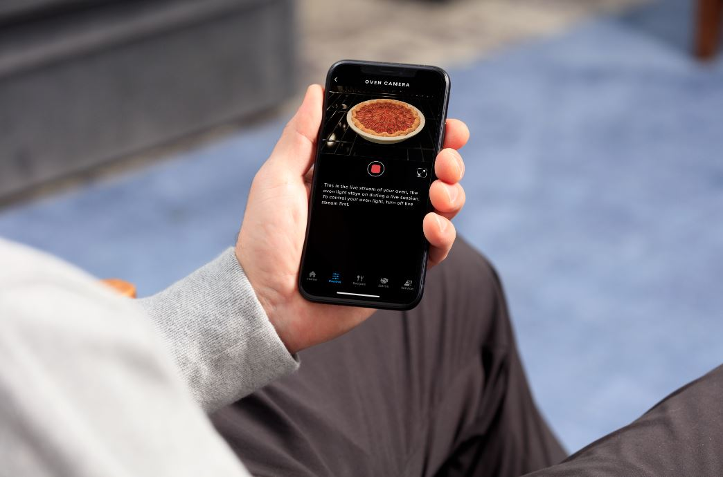 checking pie baking in the oven while on smartphone