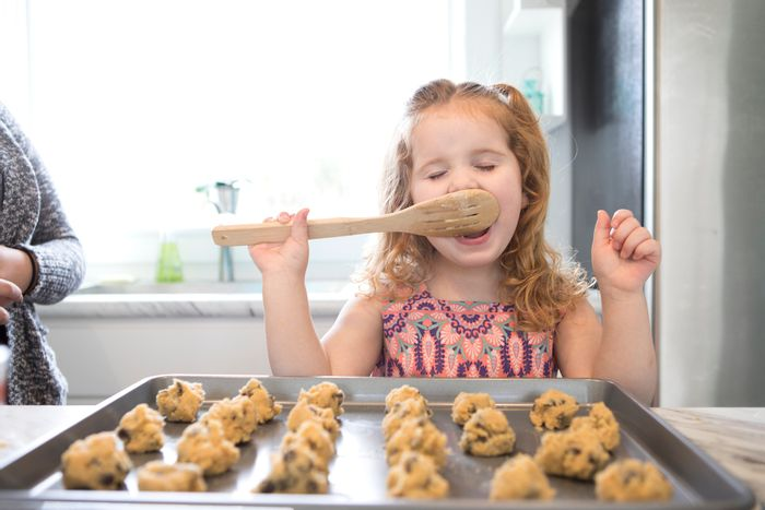 little girl licks spoon while making cookies