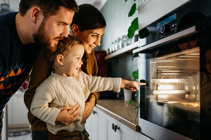 A baby and his parents look into a wall oven at their baking cookies