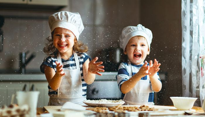 Two siblings in matching shirts, aprons and chefs hats clap flour across their cookie workstation