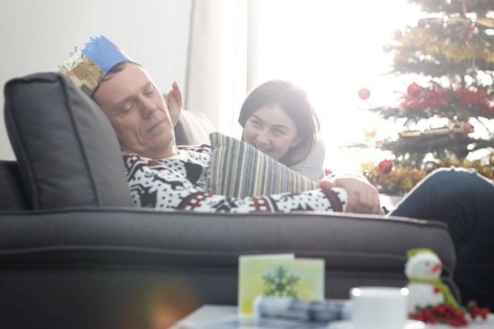 Dad naps at Christmas and is pestered by young family member