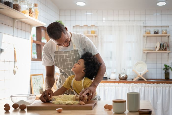 Dad and kid use rolling pin on cookie dough in bright kitchen