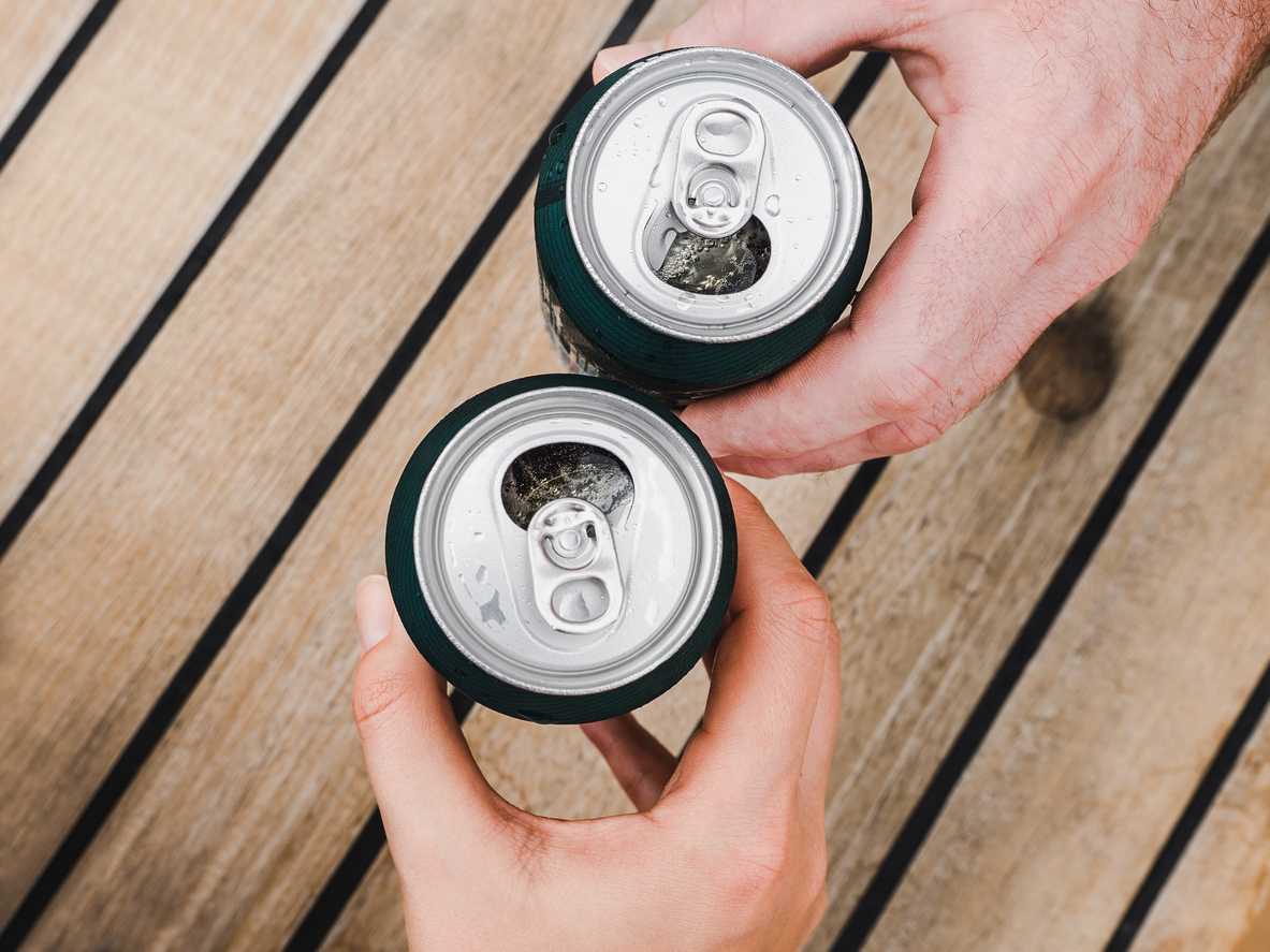 Two open soda cans clinking in a cheers