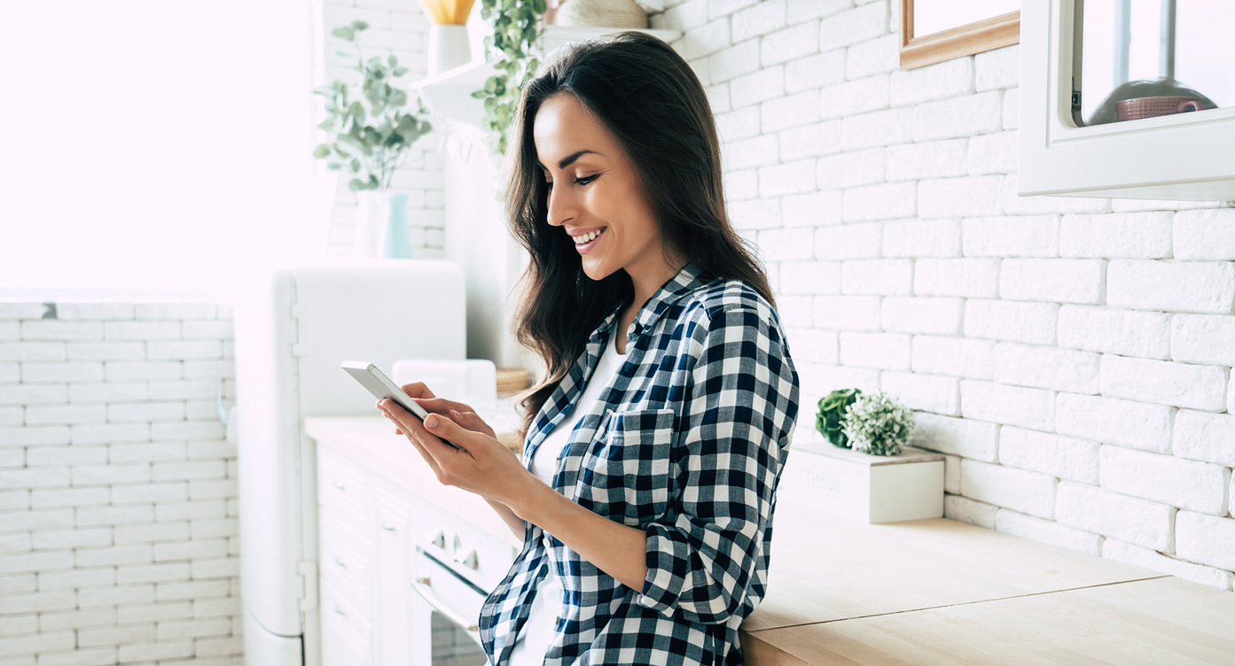 woman smiling and looking at her phone in a white kitchen
