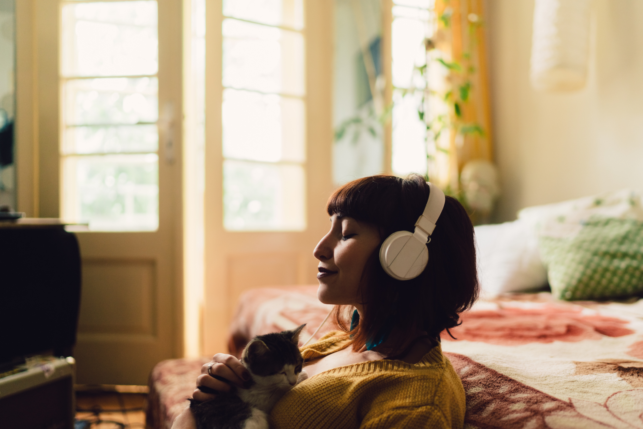 woman with headphones on holding a cat