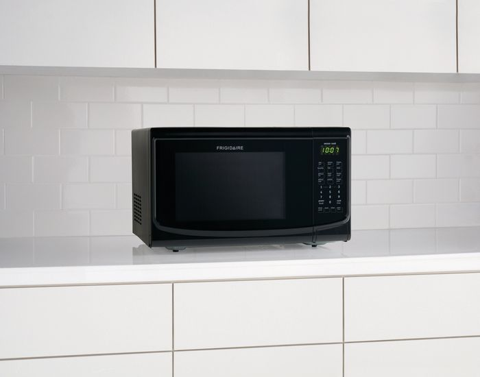 Black Frigidaire microwave sitting on a white countertop in a white kitchen.