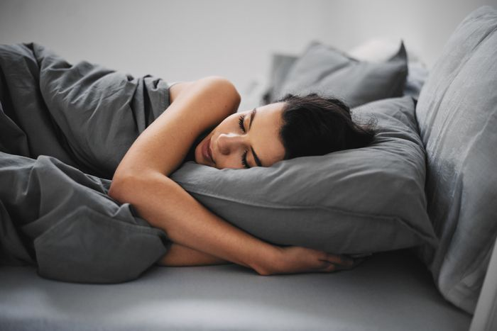 A smiling woman curls up on a bed, holding a dark grey pillow.