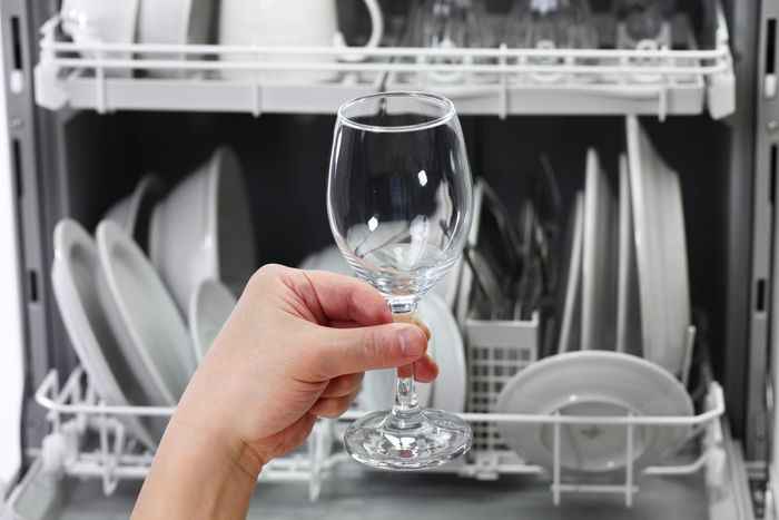 A hand holds up a perfectly clean wine glass in front of an open dishwasher full of clean dishware.