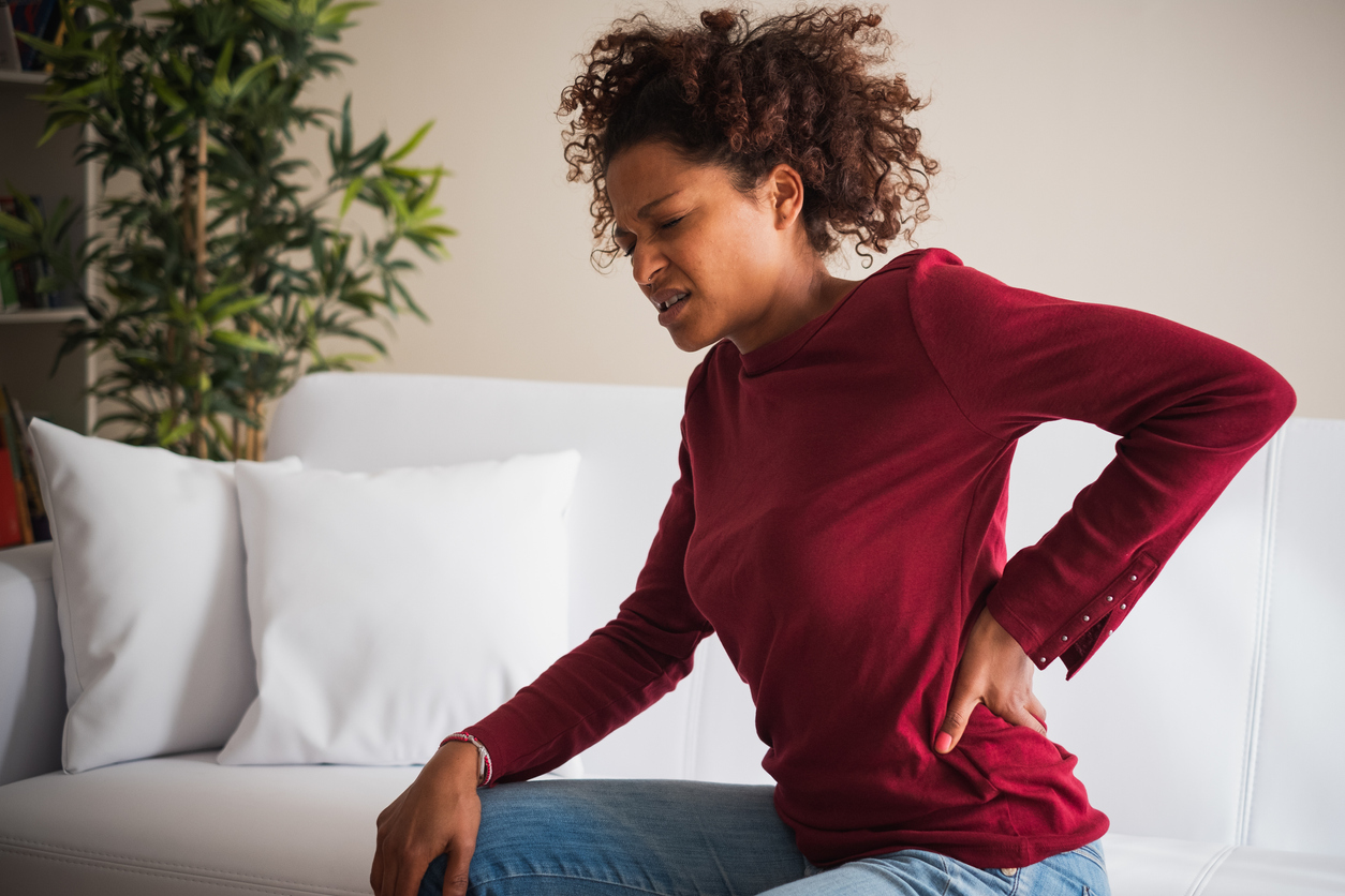 a woman sitting down and looking in pain while holding back