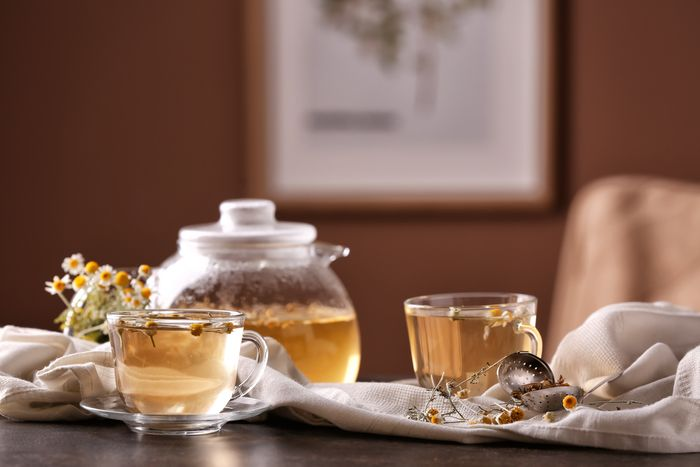A clear, glass teapot and matching glass cups filled with tea.