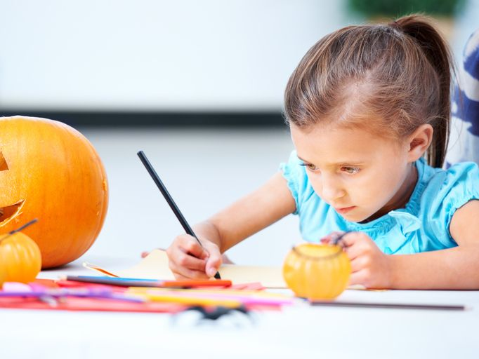 Little girl sitting at a table and coloring. A jack o' lantern is on the table beside her.