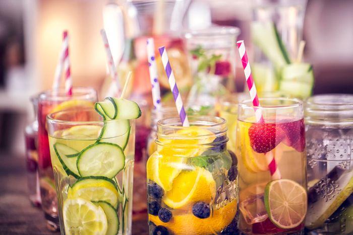 Several mason jars full of water and various fruits.