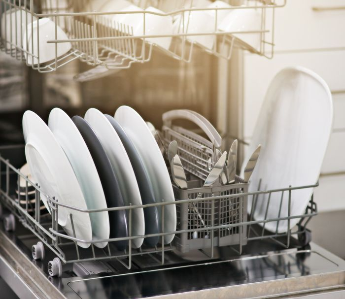 A dishwasher rack full of clean, white dishes.