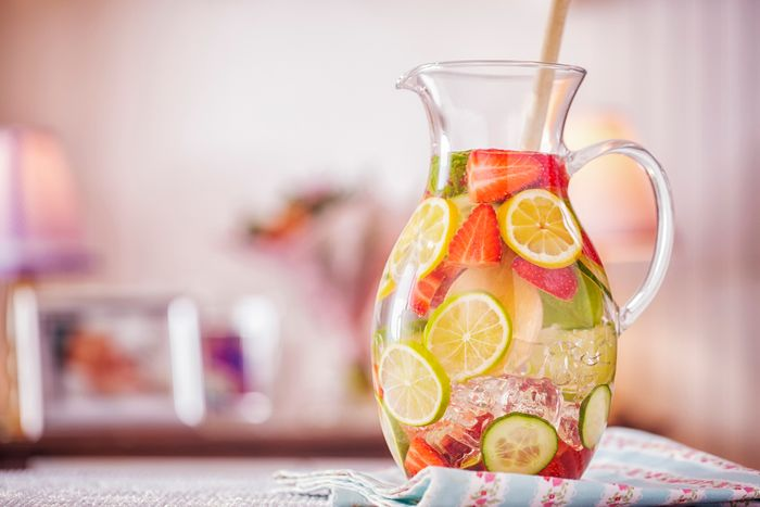 A pitcher full of water and fruit slices.