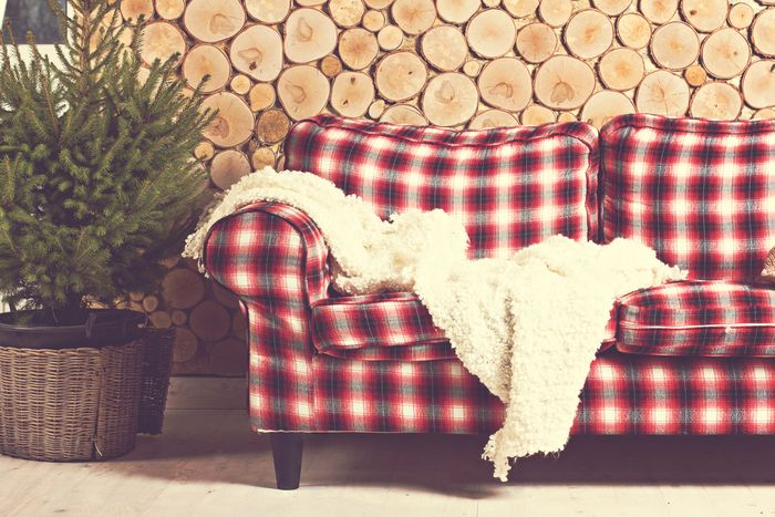 A red tartan couch in front of a wall made of wooden log cross-sections.