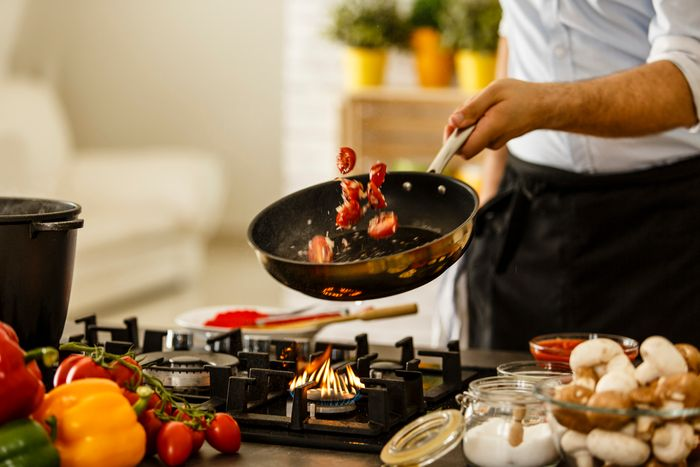 A chef tosses vegetables on a skillet over a cooktop.