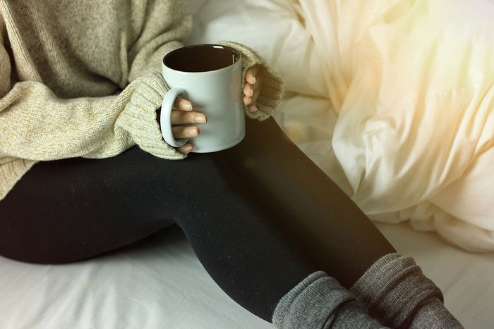 A woman sits in bed with a mug of tea in her hands.