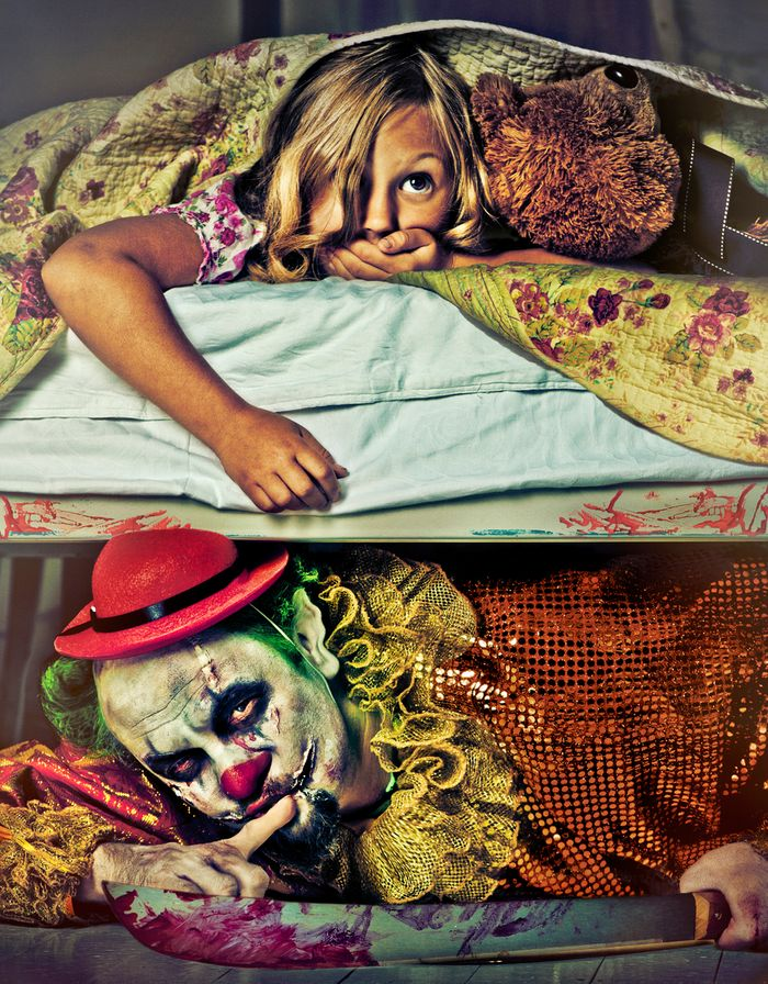 """Young girl hiding in bed with a teddy bear. A creepy clown with a bloody knife peeks out from underneath her bed, holding up his finger in a """"shh"""" motion."""