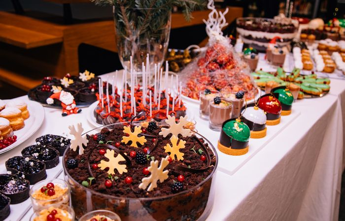A long, white tableclothed buffet of holiday-themed desserts.