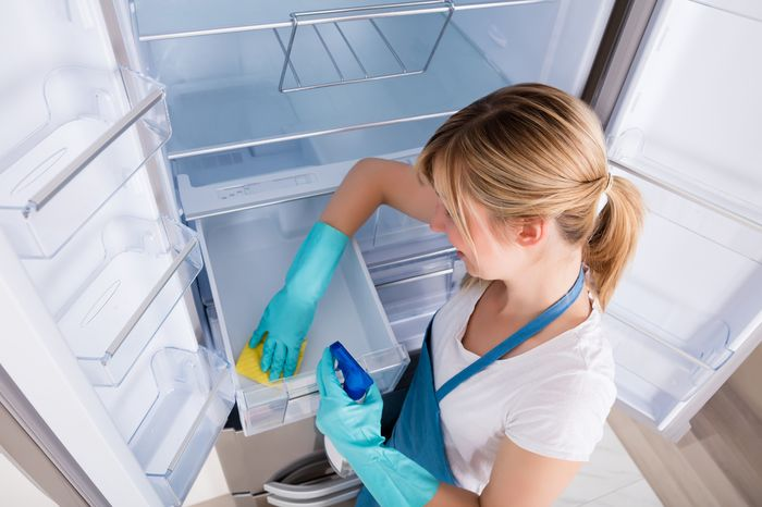 A woman wipes out a drawer of her empty refrigerator with a sponge.