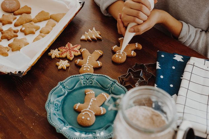 Freshly made gingerbread men lay scattered on a table while a pair of hands work at icing one cookie with a piping bag in the upper right corner.