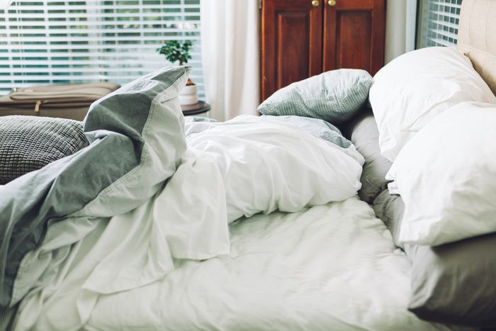 A rumpled bed with white cotton sheets.