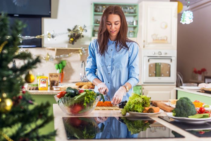 A woman chops carrots, surrounded by plates full of vegetables on her countertop. An induction cooktop is on the counter nearby her.