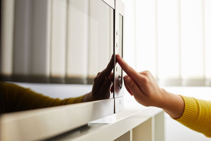 A woman's hand reaches out to touch a button on a stainless steel microwave.