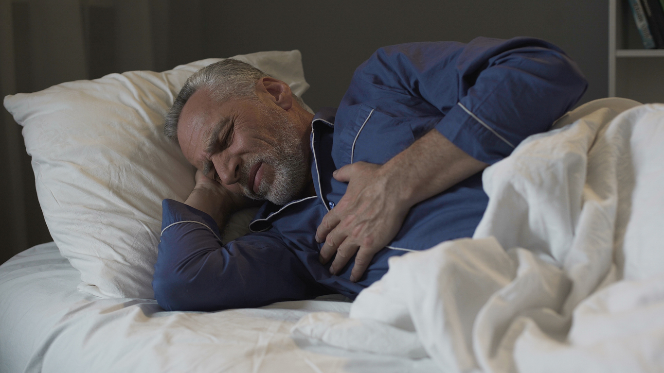 man sleeping on side has hand on chest and looks uncomfortable