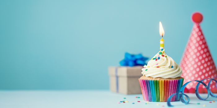 A vanilla cupcake with a single, yellow candle stuck into the frosting sits on a table in front of a blue backdrop. A small gift box and a pink party hat are in the background.
