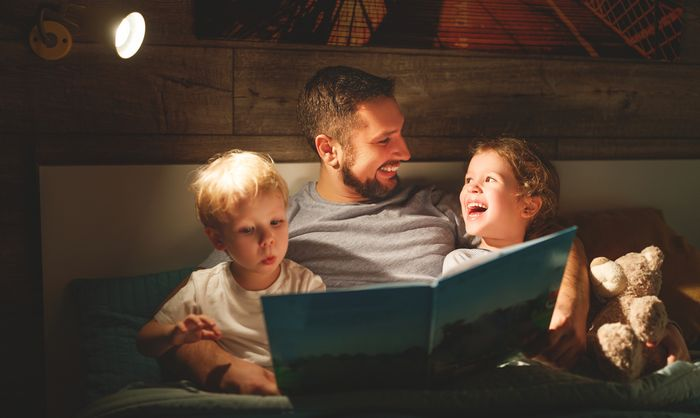 A young father sits in bed with his two young children, reading a picture book.