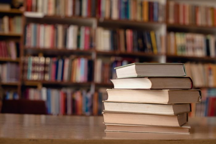 A stack of hardcover books sit on a wooden table, with shelves full of books visible in the background.