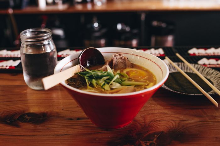 A bowl of ramen sits on a table in a restaurant.
