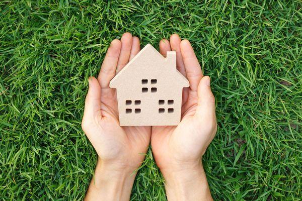 Hands holding a house-shaped figurine
