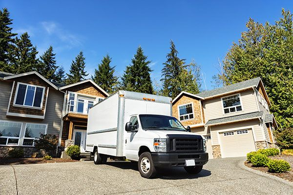 A white moving truck in a driveway