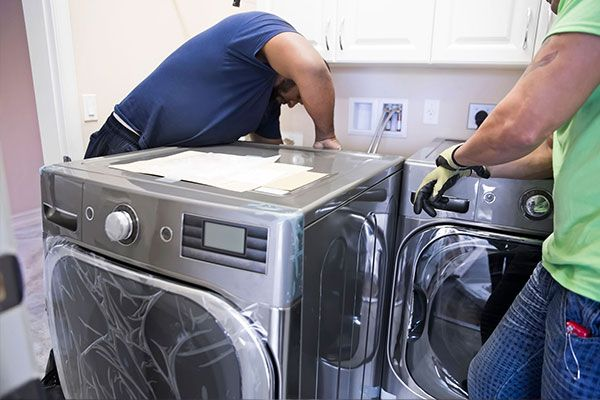 Two men installing a washer & dryer into home