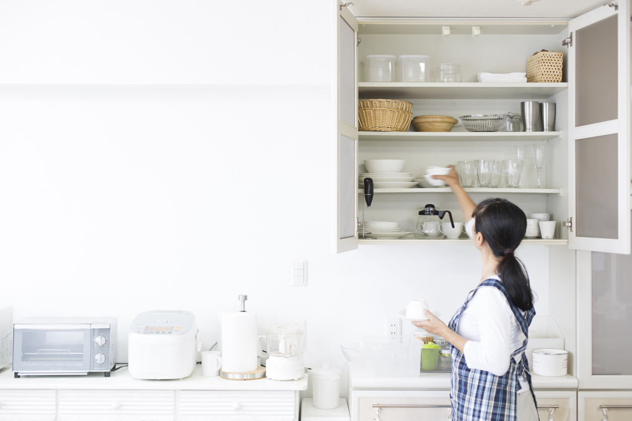woman puts cup away in cupboard